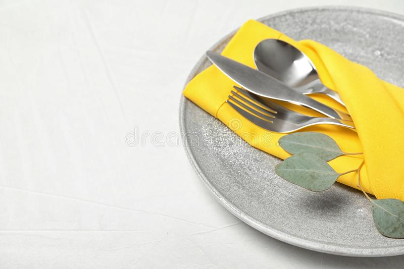 Plate with cutlery and napkin on light table, closeup. royalty free stock images
