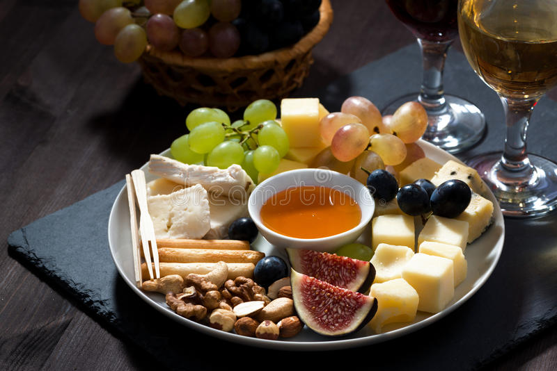 Plate with deli snacks and wine on a dark background, closeup. Horizontal stock photo