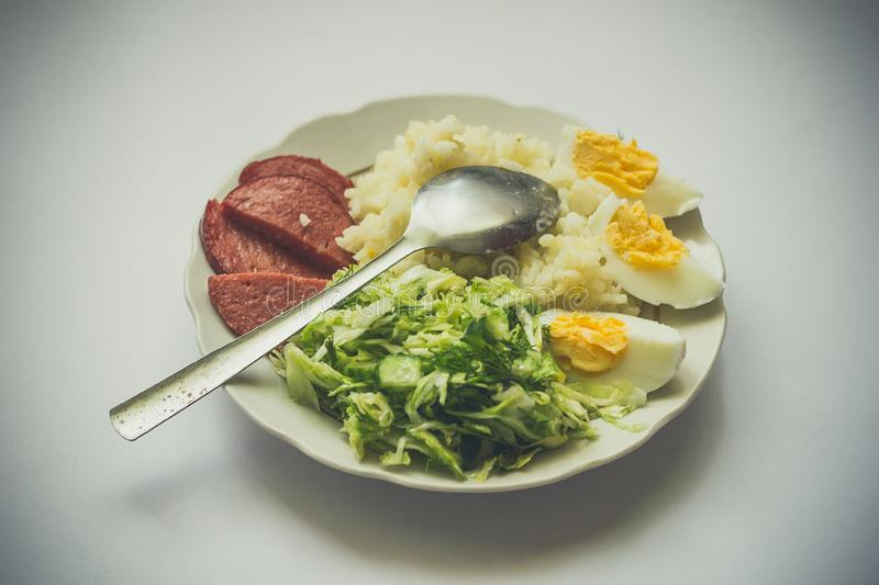 Plate with delicious breakfast with rice, sausage, eggs and salad royalty free stock image
