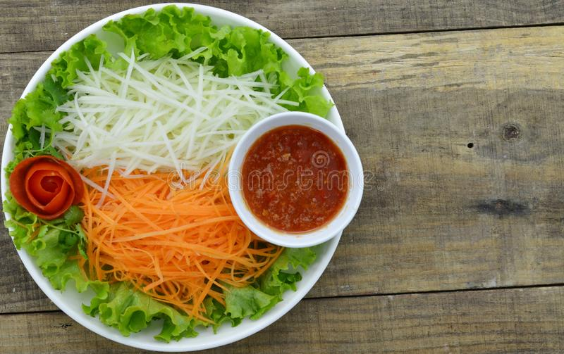 Plate with delicious carrot, kohlrabi salad and sauce on wooden table stock photography