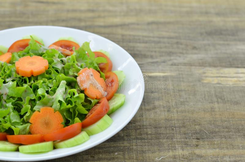Plate with delicious carrot salad on wooden background stock images