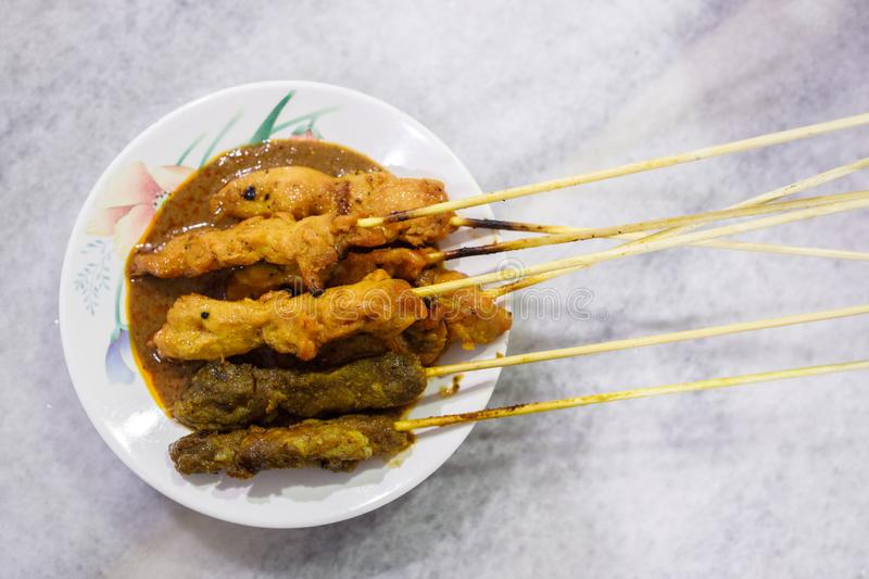 A plate of delicious chicken and lamb satay with peanut sauce. stock photography