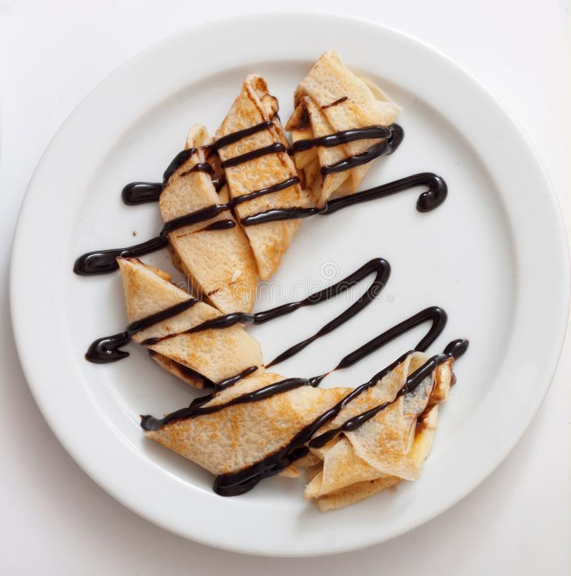 Plate of delicious crepes roll with fresh fruits and chocolate on a white plate stock photography
