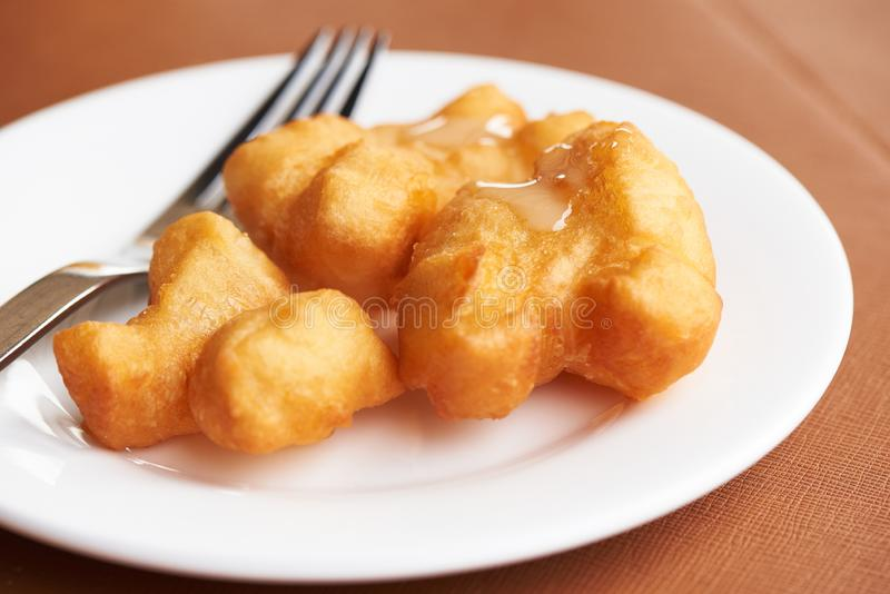 A plate of delicious deep fried dough stick. With sweetened condensed milk on top royalty free stock image
