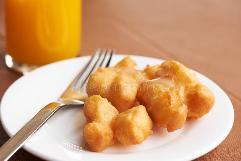 A plate of delicious deep fried dough stick with sweetened condensed milk on top. A glass of otange juice on the table stock images