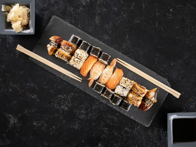 Plate of delicious healthy sushi on dark stone royalty free stock photos