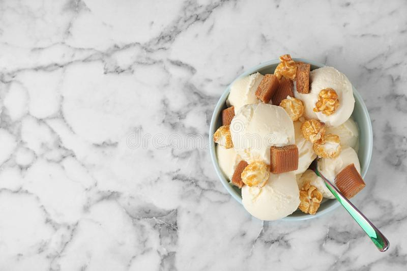 Plate of delicious ice cream with caramel candies and popcorn on white marble table. Space for text. Plate of delicious ice cream with caramel candies and stock images
