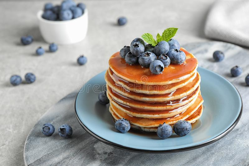 Plate of delicious pancakes with fresh blueberries and syrup on table royalty free stock photo