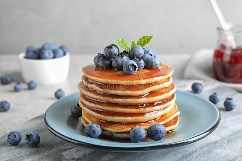Plate of delicious pancakes with fresh blueberries and syrup on grey table royalty free stock photo