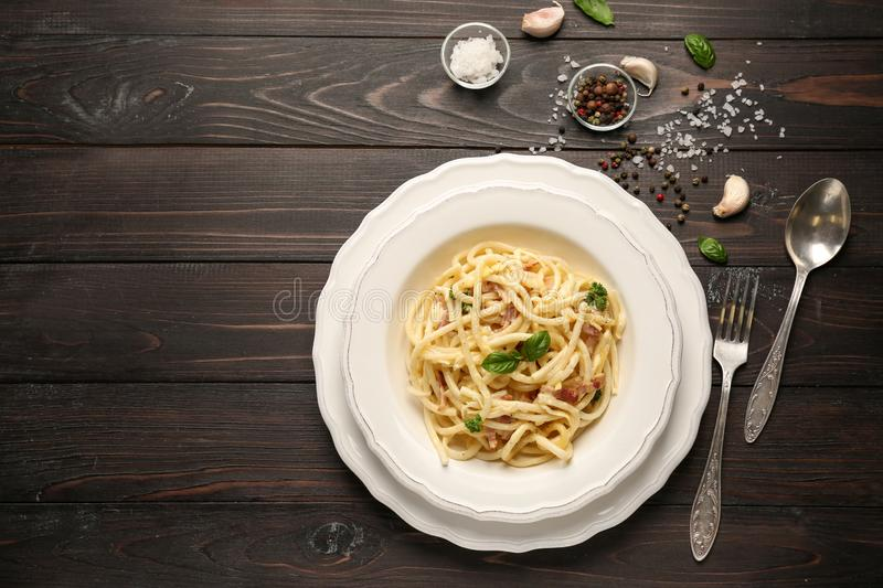 Plate with delicious pasta carbonara on dark wooden table stock image