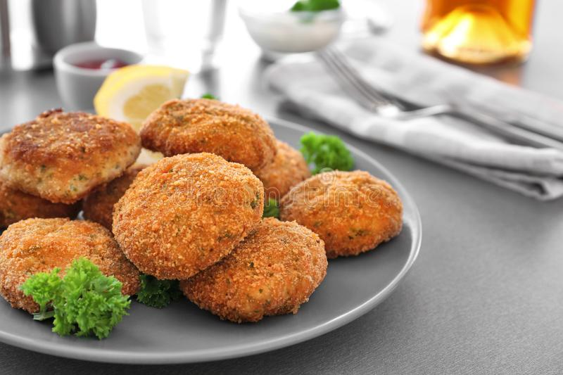 Plate with delicious salmon patties on table royalty free stock images