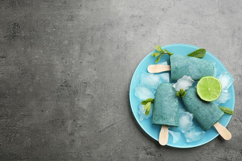 Plate with delicious spirulina popsicles and lime on grey background, top view. Space for text royalty free stock photo