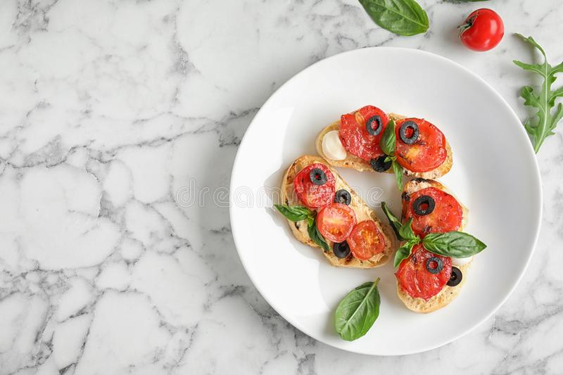Plate of delicious tomato bruschettas on white marble background. Space for text. Plate of delicious tomato bruschettas on white marble background, top view royalty free stock images