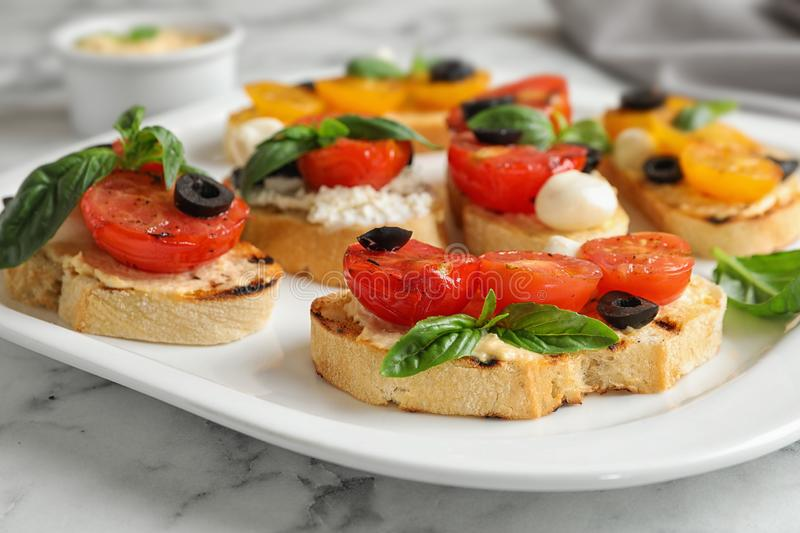 Plate of delicious tomato on white marble table, closeup. Plate of delicious tomato bruschettas on white marble table, closeup stock images