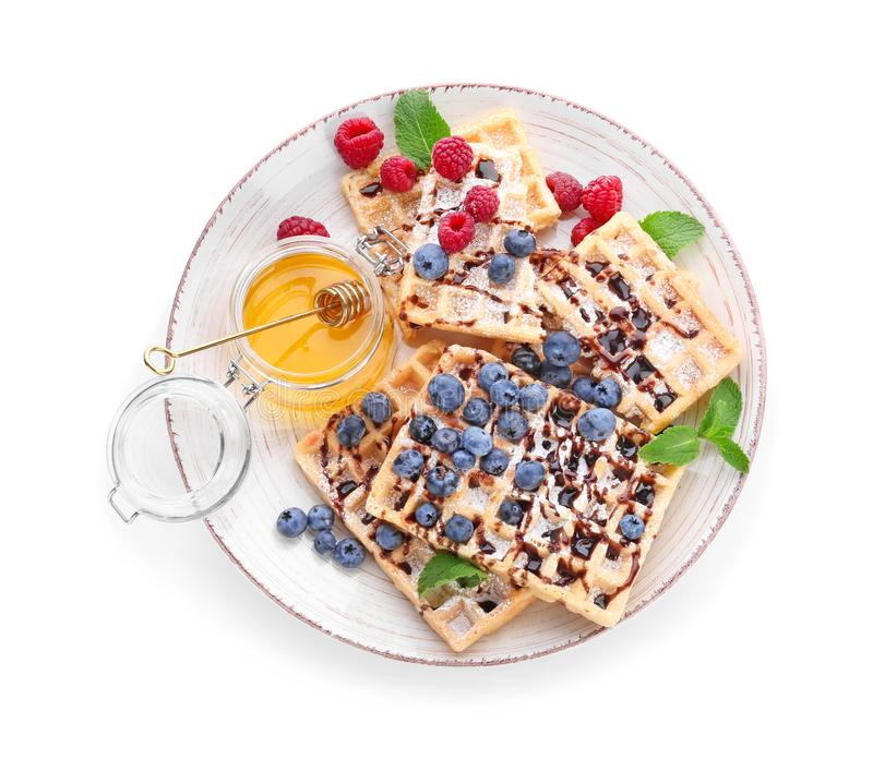 Plate with delicious waffles, berries and honey on white background stock images