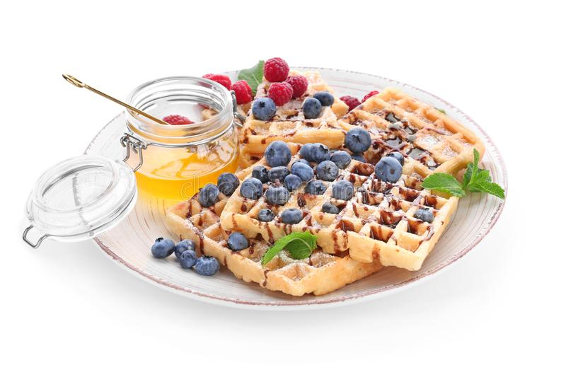 Plate with delicious waffles, berries and honey on white background royalty free stock photo