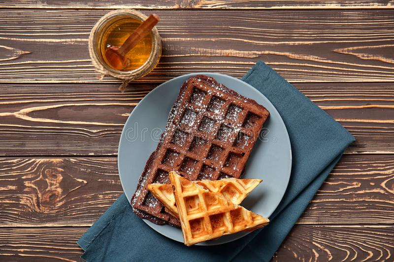Plate with delicious waffles and honey on wooden table royalty free stock photo