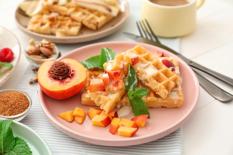 Plate with delicious waffles and peach slices on table stock photo