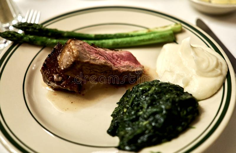 Plate of dry aged fillet mignon with asparagus and a dab of creamed spinach and mashed potatoes. A plate of dry aged fillet mignon with asparagus and a dab of royalty free stock photo