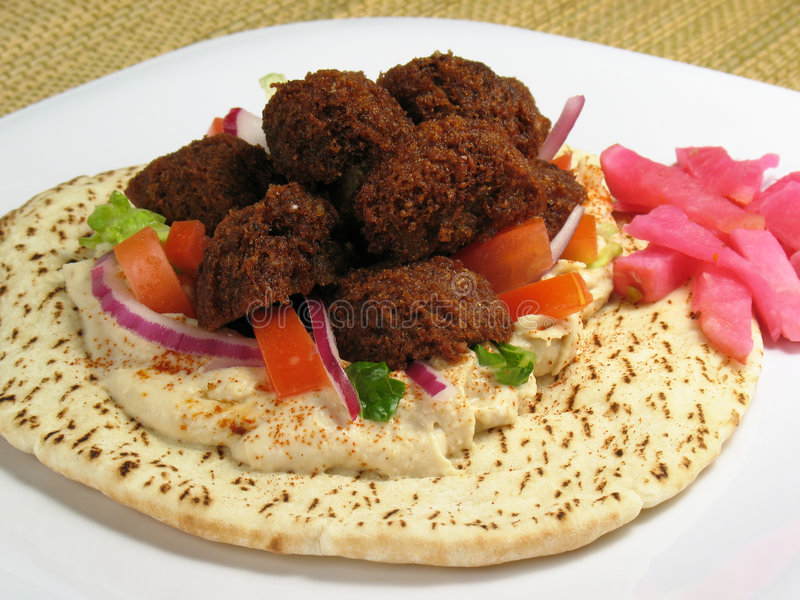 Plate With Falafels and Pita Bread. A delicious portion of falafels served on top of a pita bread with hummus, lettuce, tomato, red onions, and a side of turnips stock images