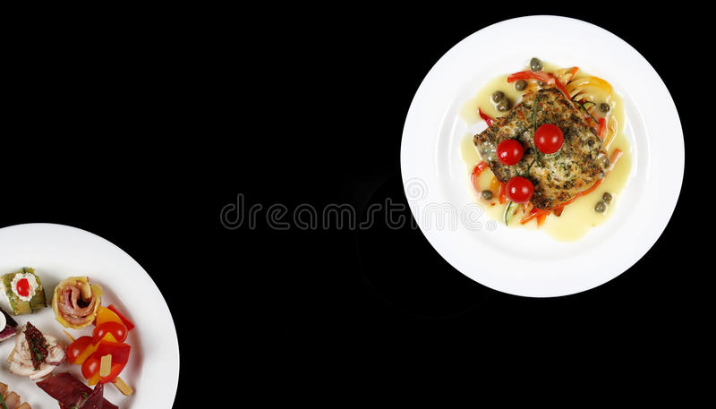 Plate with food on a black background royalty free stock image