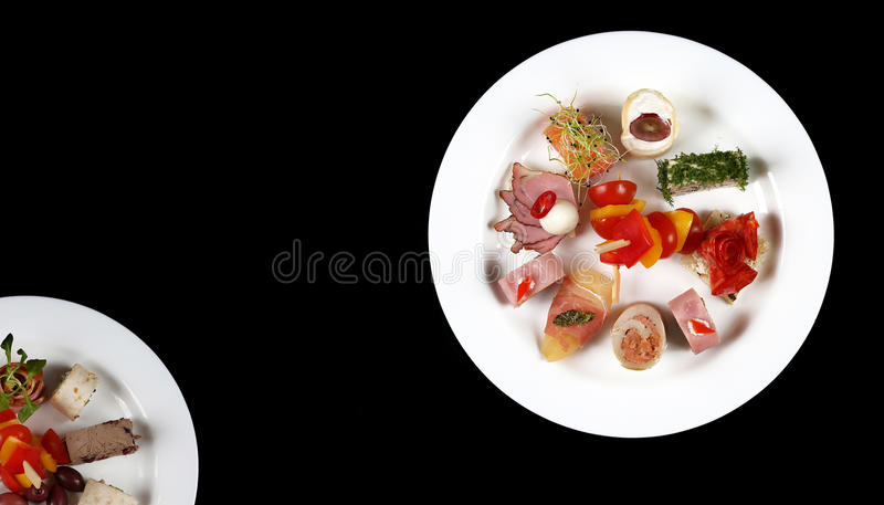 Download Plate With Food On A Black Background Stock Photo