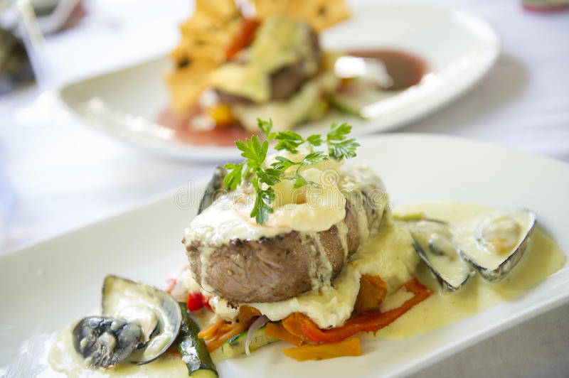 A plate of food waits to be eaten at a fine restaurant. Beef fillet plate of food stock image