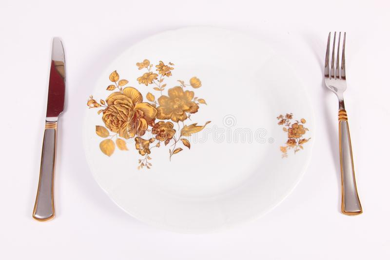 Plate, fork and knife. Dining utensils such as spoon, fork, knife and plate on a white background stock photography