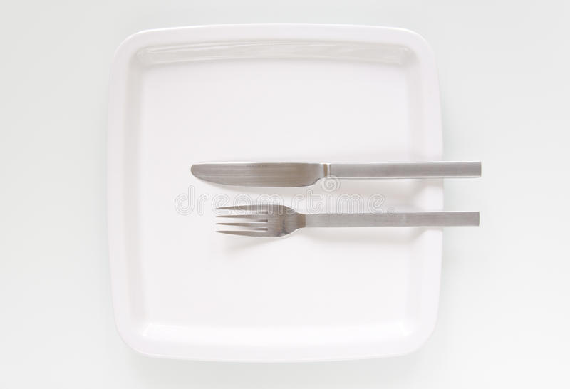 Plate, fork and knife on white. Plate, fork and knife on a white background royalty free stock photography