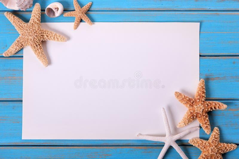 Plate-forme bleue superficielle par les agents en bois de plage de cadre d'affiche de papier de bord de la mer d'étoiles de mer v photos stock