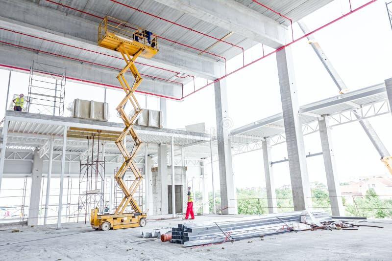 Plate-forme d'ascenseur de ciseaux sur un chantier de construction images libres de droits