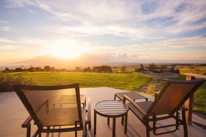 Plate-forme de chaises au coucher du soleil en dehors de la maison moderne photographie stock libre de droits