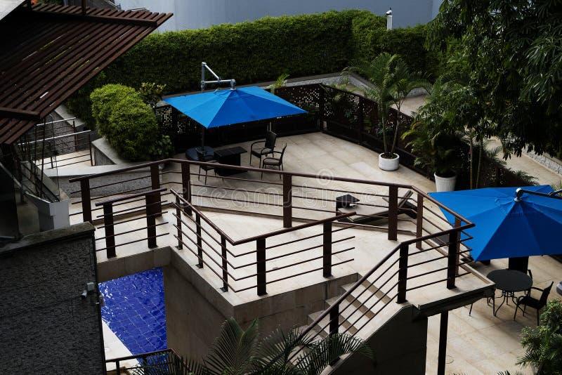 Plate-forme en bois avec les tables de billard ext?rieures avec la construction minimaliste de parapluies bleus photo libre de droits