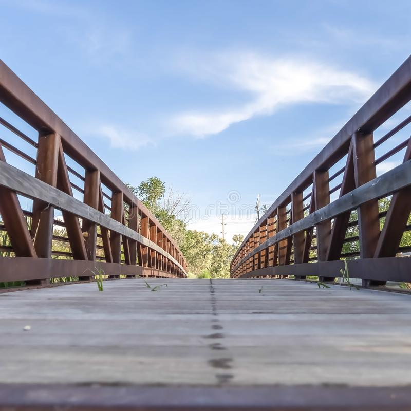 Plate-forme en bois de place et rambardes rouillées d'un pont contre le ciel bleu un jour ensoleillé image libre de droits
