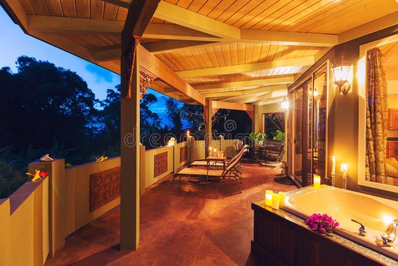 Plate-forme romantique sur la maison tropicale avec la baignoire et les bougies photo stock
