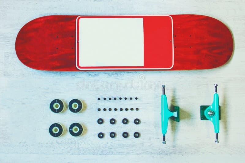 Plate-forme rouge de planche à roulettes avec l'autre équipement sur le fond en bois blanc photos stock