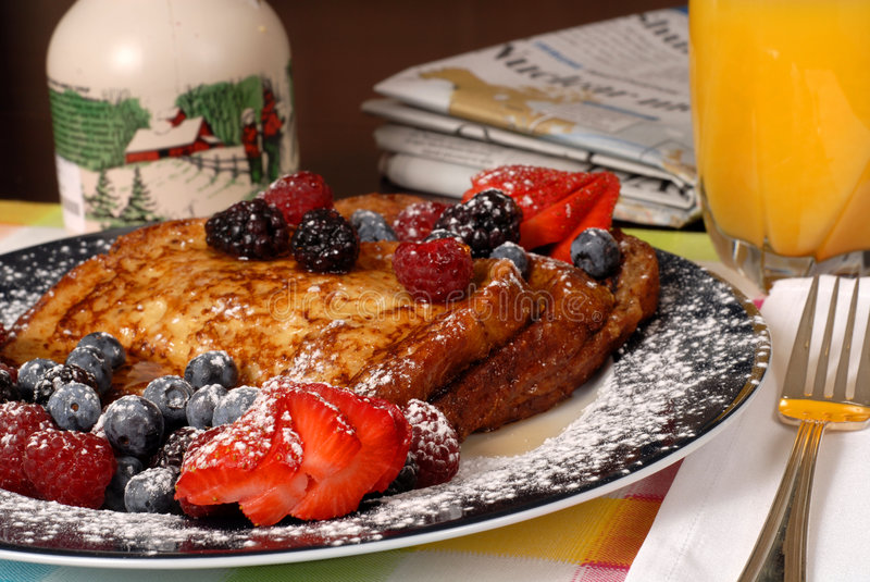 Plate of french toast with fruit and maple syrup stock photo