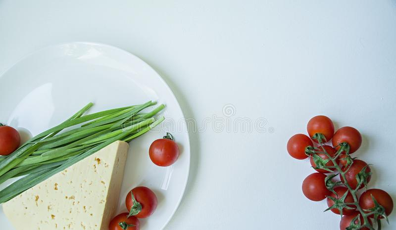 A plate of fresh cheese, a branch of fresh cherry and green garlic. White background. Space for text stock image