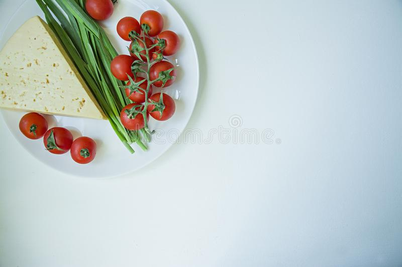 A plate of fresh cheese, a branch of fresh cherry and green garlic. White background. Space for text stock photography