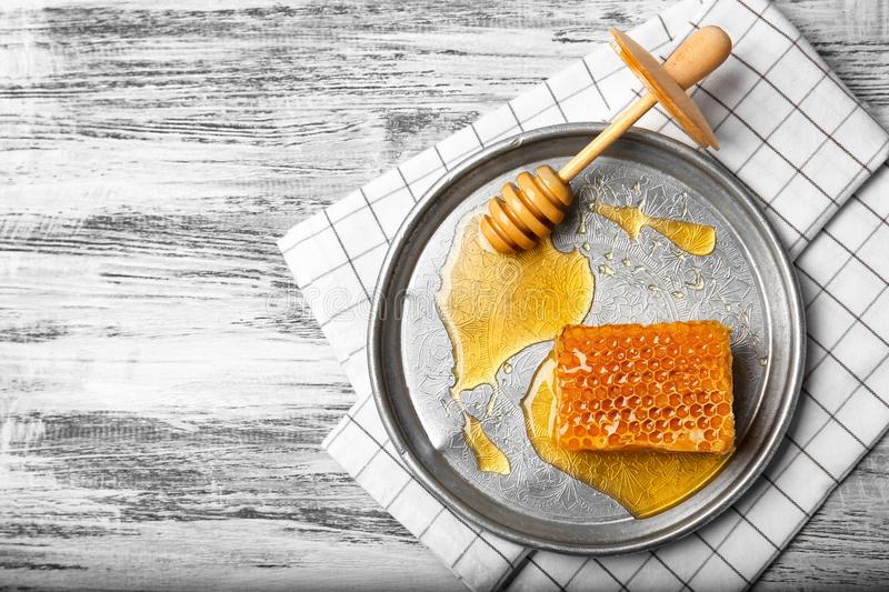 Plate with fresh honeycomb and wooden dipper on table stock photo