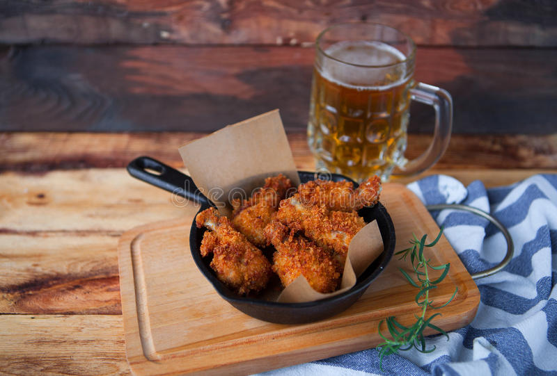 A plate of fresh, hot, crispy fried chicken with red sause on a. Blue plaid towel on a wood table. Snack to cold beer stock photography
