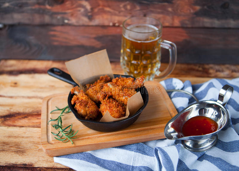 A plate of fresh, hot, crispy fried chicken with red sause on a. Blue plaid towel on a wood table. Snack to cold beer royalty free stock photography