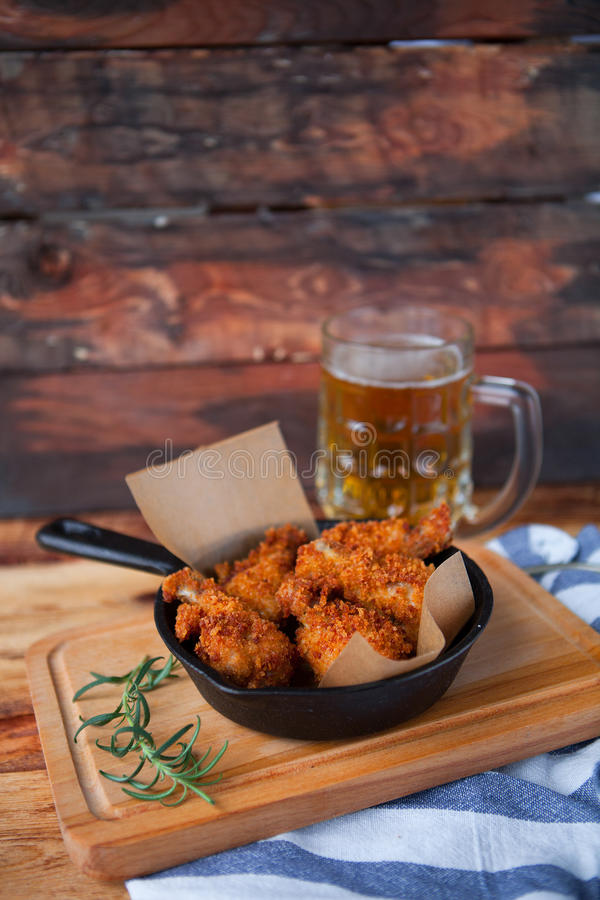 A plate of fresh, hot, crispy fried chicken with red sause on a. Blue plaid towel on a wood table. Snack to cold beer stock images