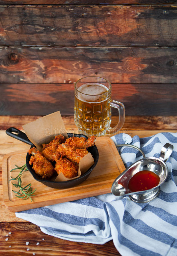 A plate of fresh, hot, crispy fried chicken with red sause on a. Blue plaid towel on a wood table. Snack to cold beer royalty free stock photo