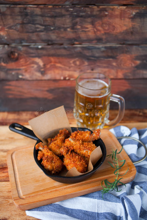 A plate of fresh, hot, crispy fried chicken with red sause on a. Blue plaid towel on a wood table. Snack to cold beer stock photo