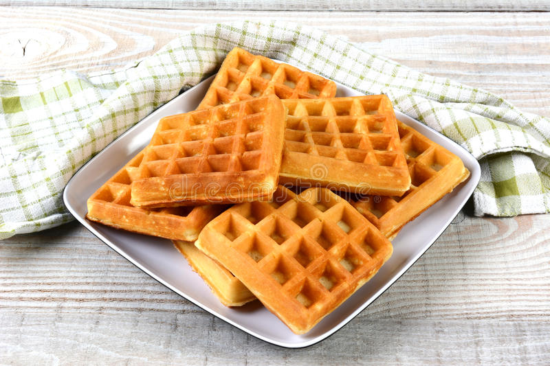 Plate of Fresh Made Waffles. A plate of fresh made waffles on a rustic farmhouse style table royalty free stock images