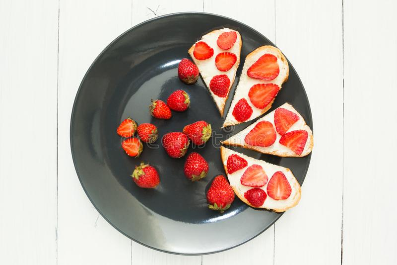 A plate of fresh organic strawberry sandwiches on a white table. Top view stock photos