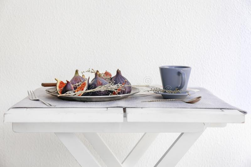 Plate with fresh ripe purple figs and cup of tea on table royalty free stock photo