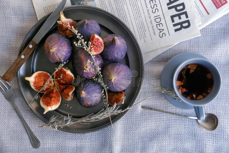 Plate with fresh ripe purple figs and cup of tea on table, top view royalty free stock images