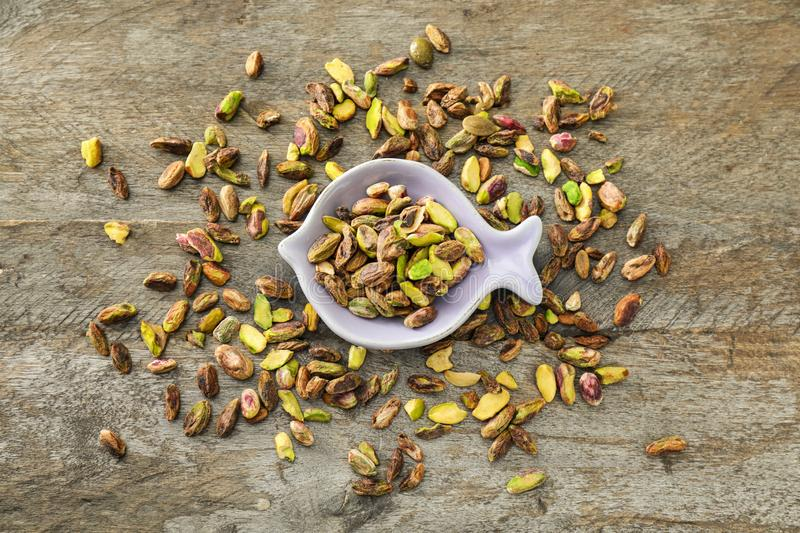 Plate with fresh tasty pistachio nuts on wooden background royalty free stock photos